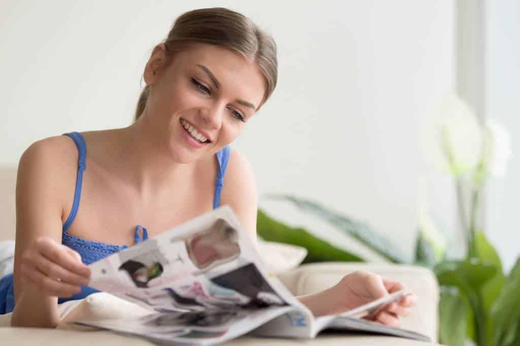 femme rigolant en lisant un magazine